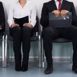 professionals sitting in chairs outsde of hiring manager office