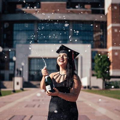 Hispanic woman college graduate in graduation cap pops open a bottle of sparkling cider