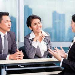 Latina woman talking to interviewers about a job opportunity