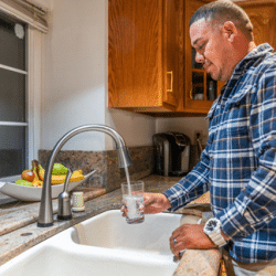 Hispanic man fills a glass of water at his kitchen sink