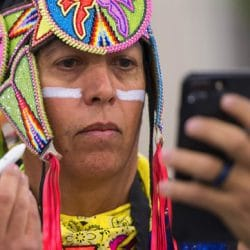 U.S. Army veteran, Brian Hammill of the Ho-Chunk Nation, applies face paint before grand entry at the 28th Annual Heard Museum World Championship Hoop Dance Contest at the Heard Museum