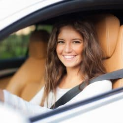 young womandriving with window down and smiling