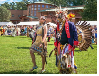 Jamestown Powwow dancers with traditional American Indian dress perform on field