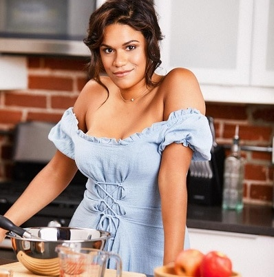 Justina Adorno in the kitchen posing with cookware and food