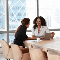 two women talking at a conference table