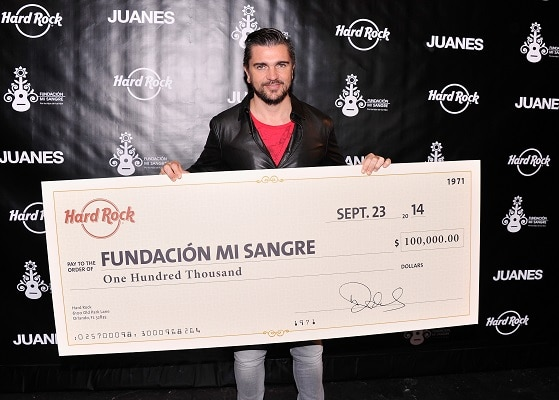 Juanes holds his big donation check for his Fundacion Mi Sangre foundation