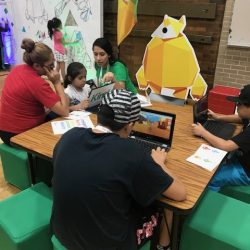 Children playing computer game on laptops at a table