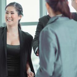 early to work employee is smiling and conversing with other employees
