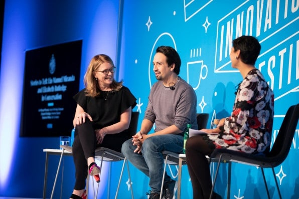 Lin-Manuel Miranda seated onstage with guest two interviewers