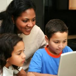 Latino family in kitchen on the computer