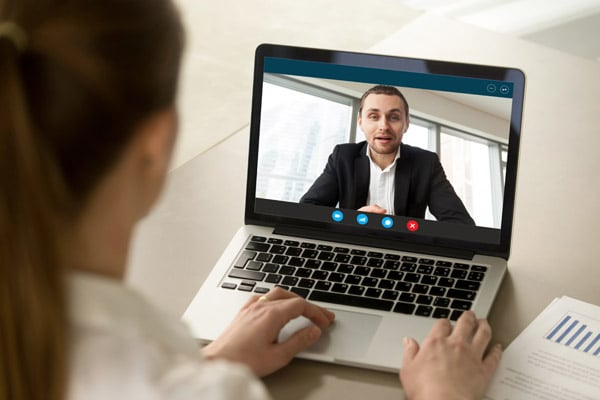 Back view of female employee talk with male businessman on webcam laptop conference, woman worker with man employer brainstorm on video call from home, online