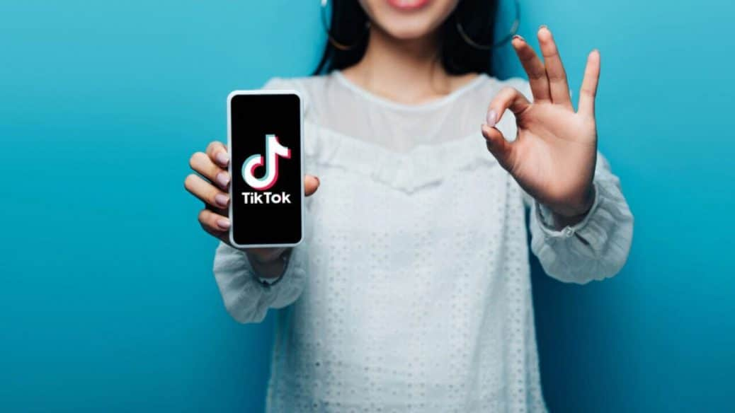 tikTok text on smartphone with girl giving the ok sign