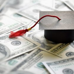 Graduation mortar board cap on one hundred dollar bills concept for the cost of a college and university education loans