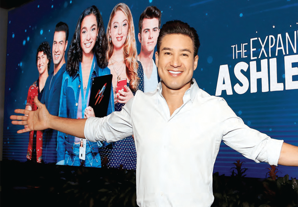 Mario Lopez pictured with arms spread out, smiling, Ashley Garcia poster in background with pictures of the cast