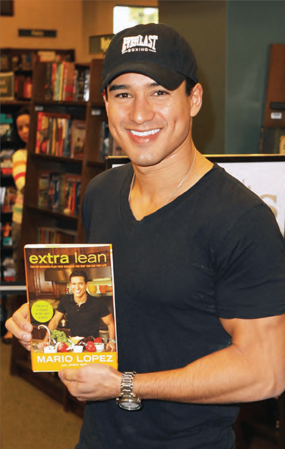 Mario Lopex holding up his book Extra Lean